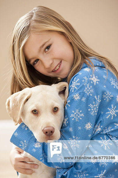 Portrait of girl (10-11) embracing Labrador