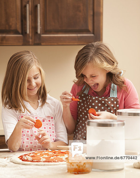 Two girls (10-11) preparing pizza in kitchen
