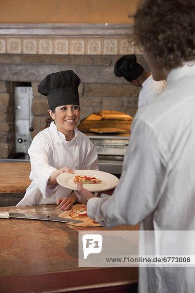 geben  Scheibe  Pizza  Köchin