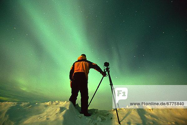 Photographer under the Aurora Borealis  Northern Yukon