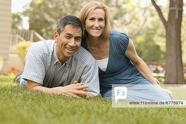 USA  Utah  Provo  Portrait of smiling mature couple sitting on lawn in garden