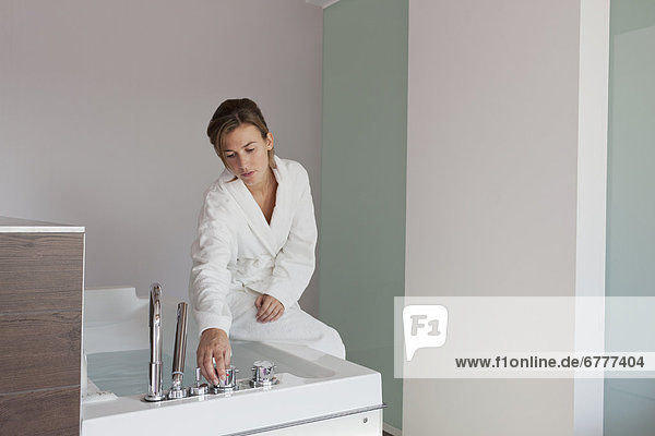 Woman in bathrobe pouring water into tub