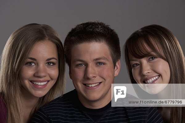 Portrait of teenage boy (16-17) and girl (16-17) with young friend  studio shot