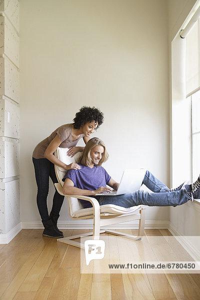 Young woman looking at man using laptop at home