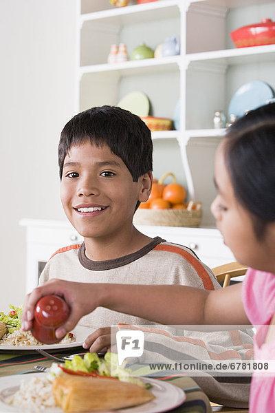 Portrait  lächeln  Junge - Person  am Tisch essen  5-9 Jahre  5 bis 9 Jahre  10-11 Jahre  10 bis 11 Jahre  Mädchen  Tisch