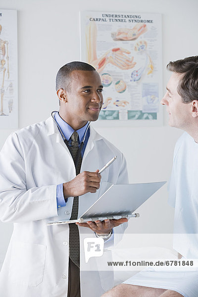 Male doctor talking to patient in hospital