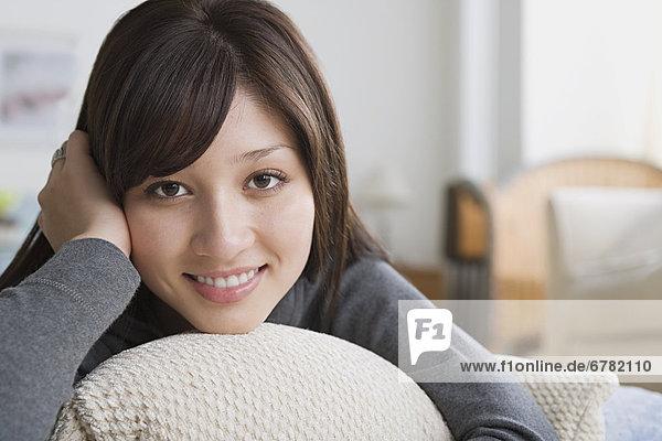 Junge Frau liegt auf Sofa  Kopf auf Händen  lacht in Kamera  Porträt