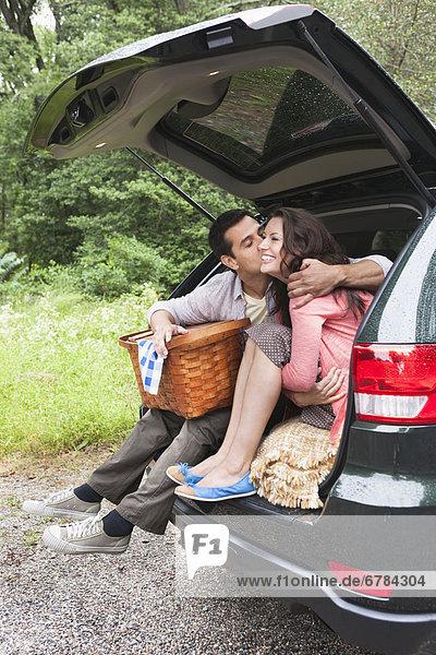 sitzend  Fröhlichkeit  Auto  Picknick  Korb  Kofferraum