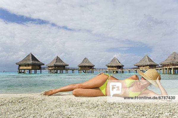 Französisch Polynesien  Tuamotu-Inseln Rangiroa Atoll  Frau Faulenzen am Strand  Luxus Resort Bungalows im Hintergrund.