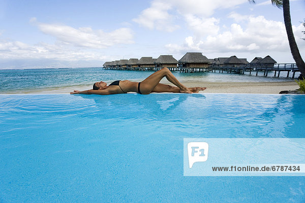 French Polynesia  Moorea  Woman relaxing at resort poolside  Luxury resort bungalows in background.