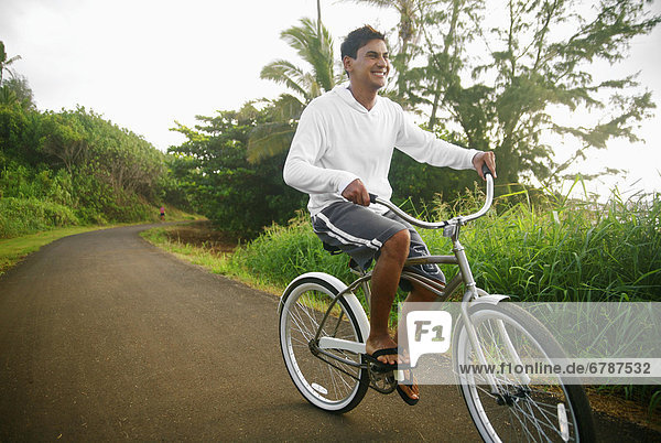 Hawaii  Kauai  Kealia Beach  junger Mann mit dem Fahrrad auf dem Radweg.