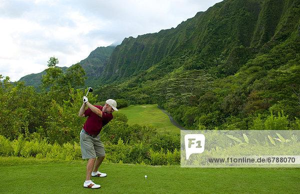 Hawaii  Oahu  Honolulu  Ko'olau Golf Course  Man driving on the 15th hole with beautiful mountain view.