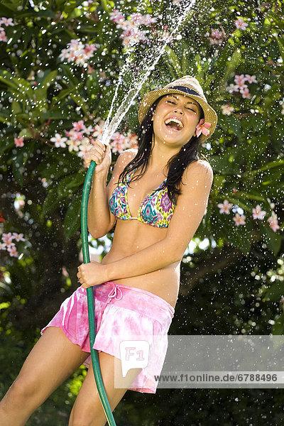 Hawaii  Oahu  junges Mädchen spritzendes Wasser auf sich selbst mit Schlauch.