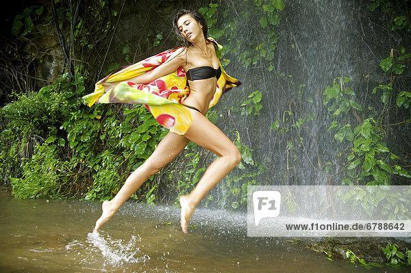 Hawaii  Kauai  Haena Falls  Attractive young woman on jumping in the falls.