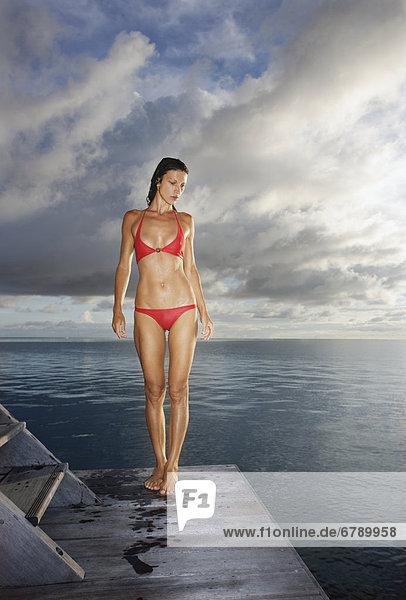 Französisch-Polynesien  Moorea  attraktive junge Frau stehend auf einem Dock nach Schwimmen im Ozean.