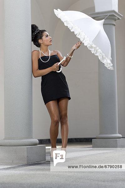 Junge Frau mit Hochsteckfrisur  kurzem schwarzem Kleid  hohen Schuhen und weißem Schirm lehnt sich an Säule