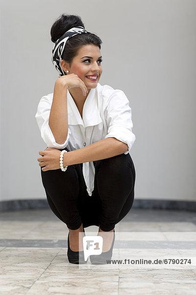 Lächelnde junge Frau mit Hochsteckfrisur  weißem Hemd  schwarzen Leggins und hohen Schuhen