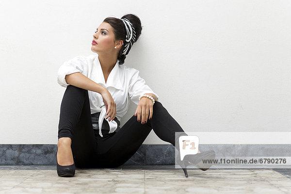 Junge Frau mit Hochsteckfrisur  weißem Hemd  schwarzen Leggins und hohen Schuhen posiert sitzend