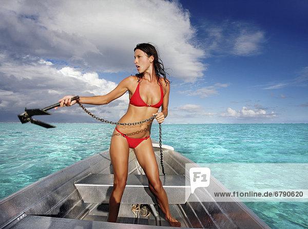 Französisch-Polynesien  Tahiti  Bora Bora  Frau auf einem Boot löst Anker.