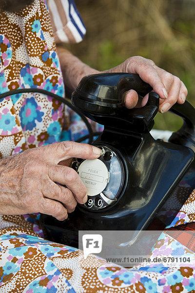 Alte Frau wählt auf historischem Telefon