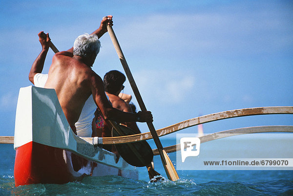Outrigger canoe paddling  Close-up view from behind.
