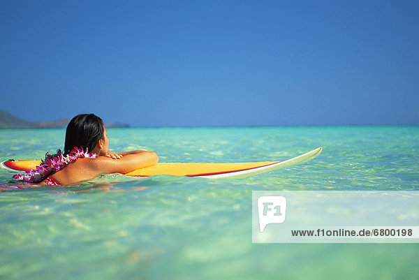 Hawaii  Oahu  Lanikai  Woman resting on surfboard looking out on clear teal water.