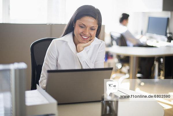 Businesswoman working on laptop  businessman in background