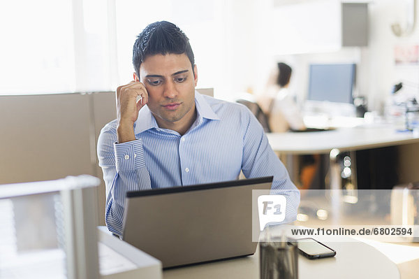Businessman working on laptop  businesswoman in background