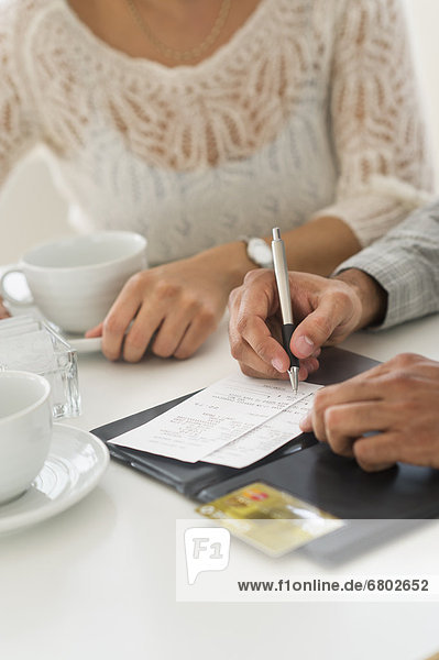 Couple enjoying tea  man signing receipt