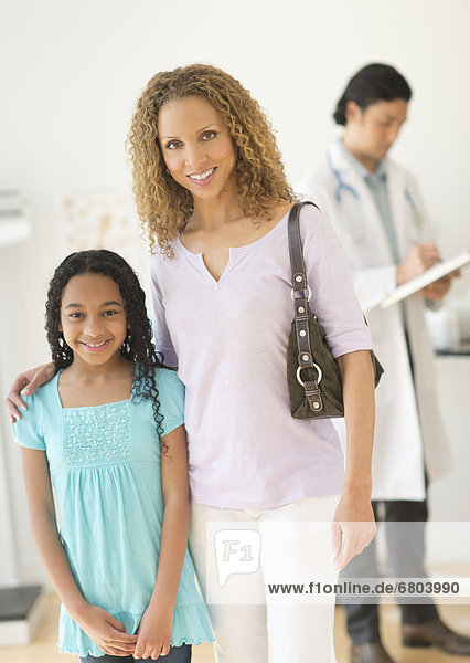 Portrait of mother with daughter (12-13) at doctor's office