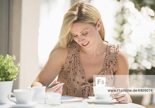 Frau  schreiben  Cafe  Zeitschrift  Außenaufnahme  Tisch