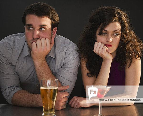 Bored couple sitting at bar counter