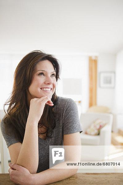 Frau am Tisch sitzen und lächelnd