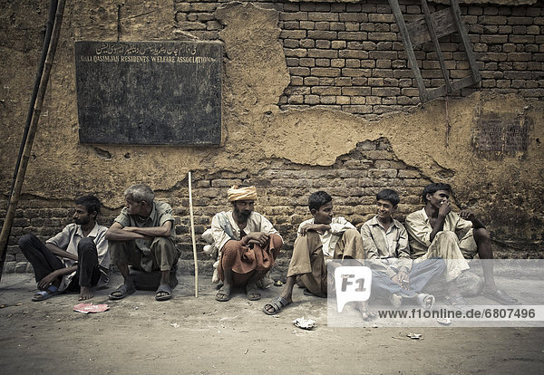 A Group Of Male Laborers Sitting In A Row On The Street  Delhi India