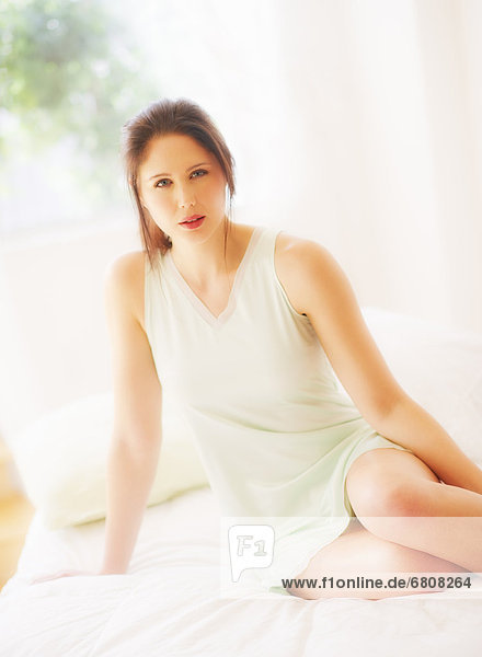 Portrait of young Woman sitting on bed