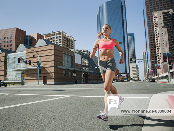 USA  California  Los Angeles  Young woman running on city street