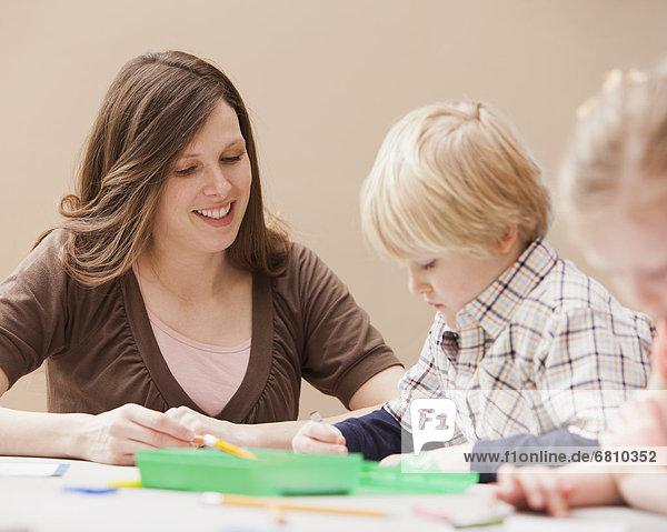 Mid adult woman teaching boy (4-5) drawing in kindergarten