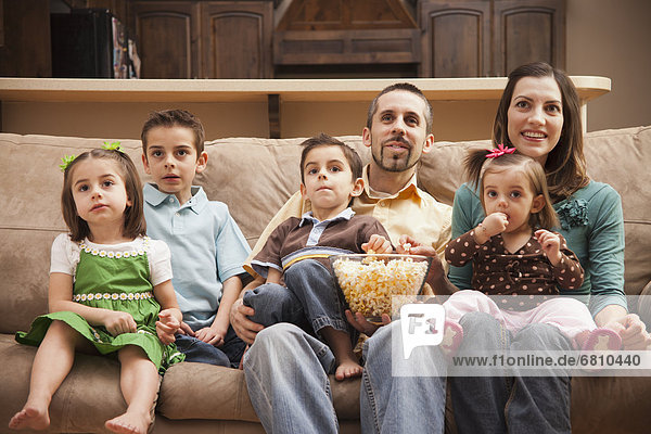 sitzend  sehen  frontal  Fernsehen  Ansicht  Couch  5-6 Jahre  5 bis 6 Jahre  5-9 Jahre  5 bis 9 Jahre  essen  essend  isst  Popcorn