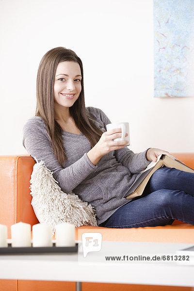 junge Frau junge Frauen Couch lächeln vorlesen