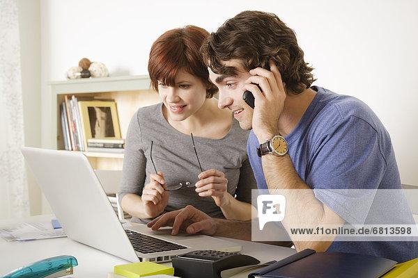 Junges Paar benutzt einen Laptop