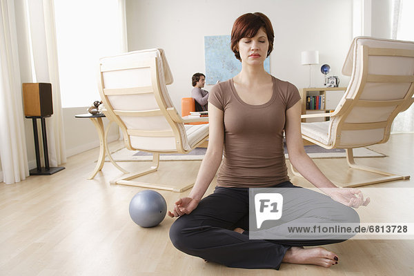 Young woman meditating  man relaxing in background