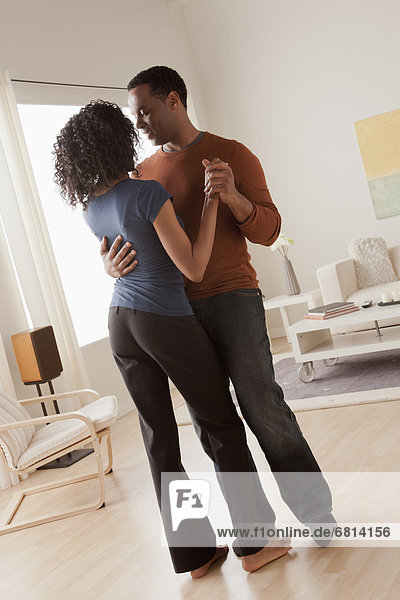Mid adult couple dancing at home