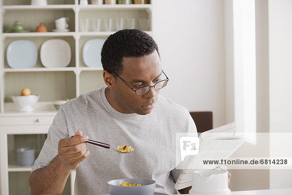 Mann Mittelpunkt essen essend isst Erwachsener Frühstück Zeitung vorlesen