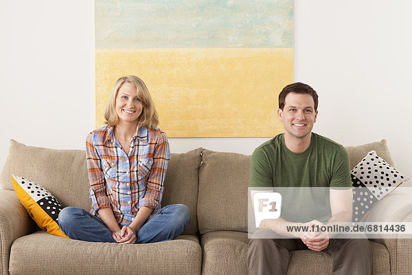 Smiling mid adult couple sitting on sofa