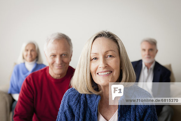 Two senior couples on sofa  smiling woman in foreground