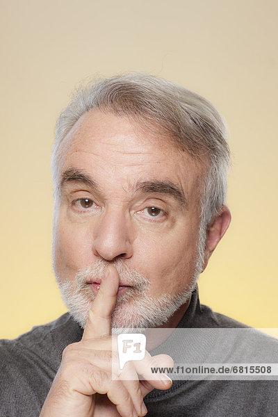 Studio shot of senior man with finger on her lips