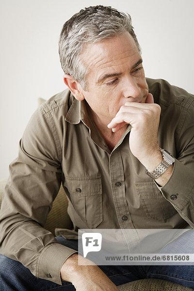 sitzend  Mann  Nervosität  Couch  reifer Erwachsene  reife Erwachsene