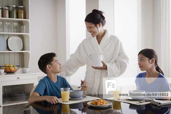 Mother serving breakfast to son and daughter