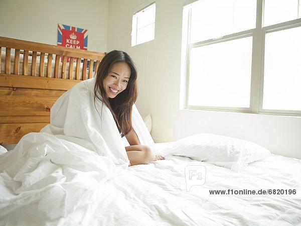 Junge Frau sitzt auf dem Bett