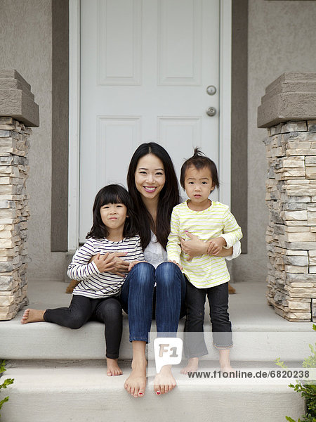Portrait of mother sitting on doorsteps with two daughters (2-3  4-5)